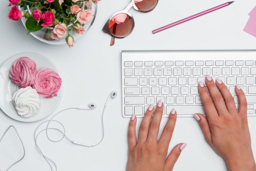 white keyboard with pink flowers on a desk and a hands with pink fingernail polish