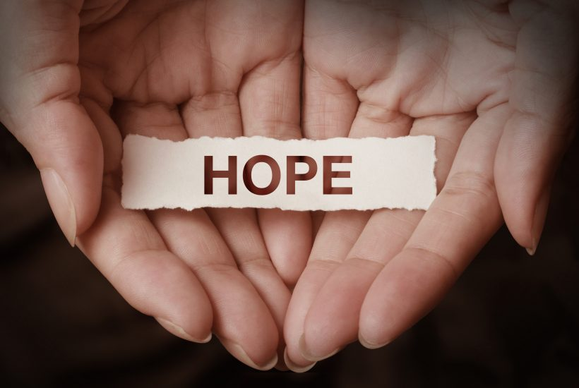 strip of paper that says hope in the palm of a woman's hand