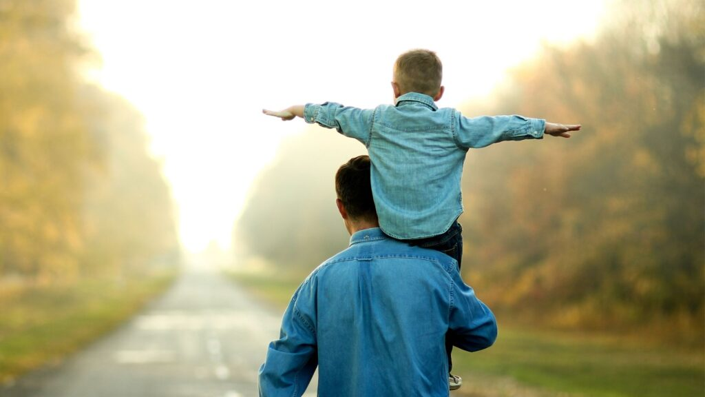 toddler sitting on his dad's shoulder while dad is walking down the road