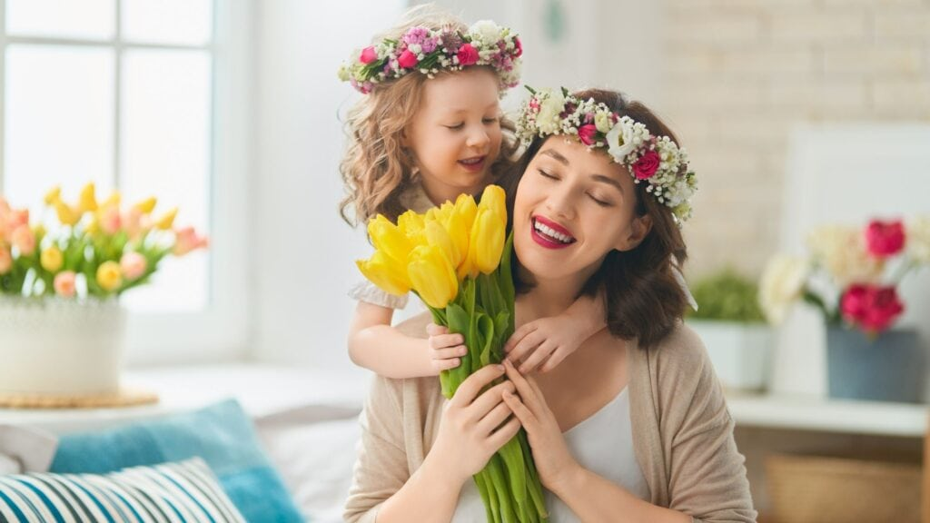 happy mother and toddler daughter with flower crowns on their heads