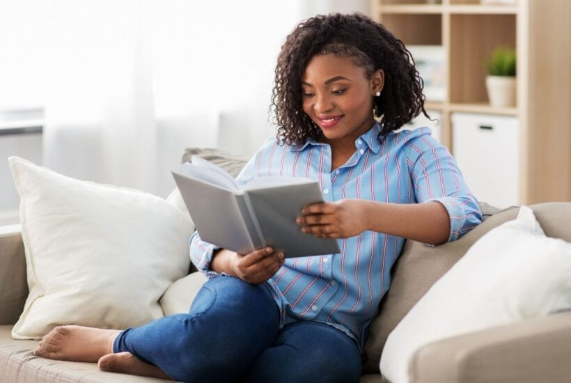 african american woman sitting on a couch reading a book
