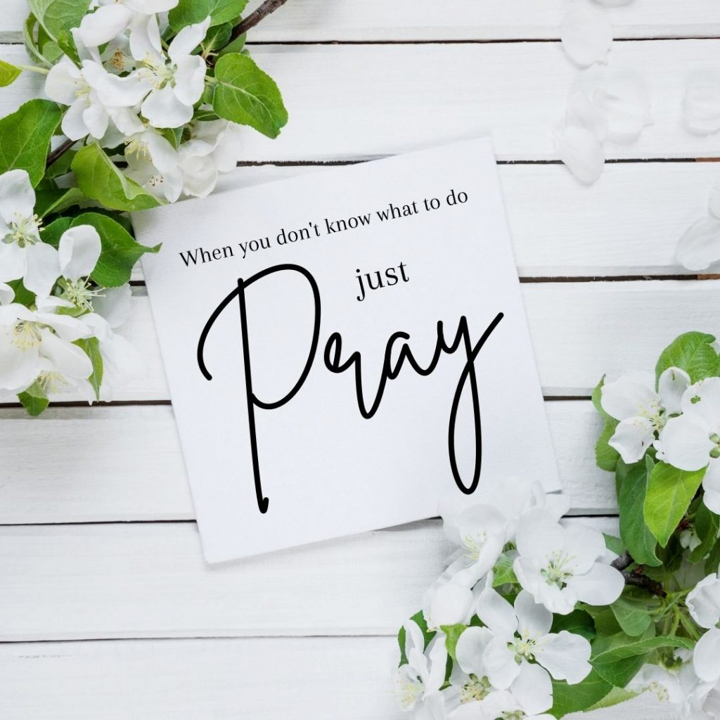 just pray written on a white sticky note on a wooden background with white flowers