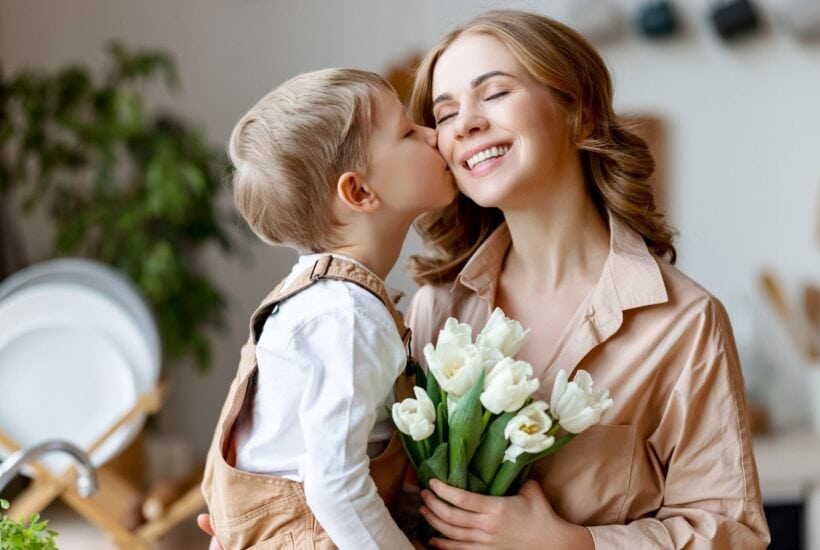 young boy giving his mom a kiss while she is smiling