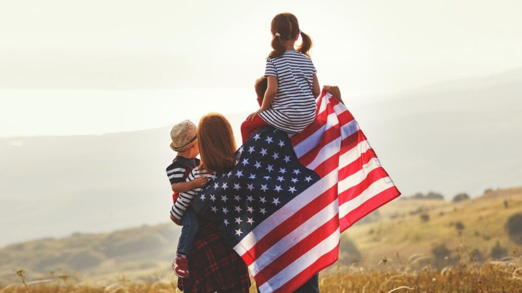 family of four standing outside looking out with an american flag draped across their backs