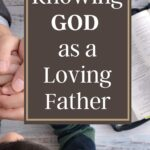 father holding his son's hands across a table with a bible laying next to them