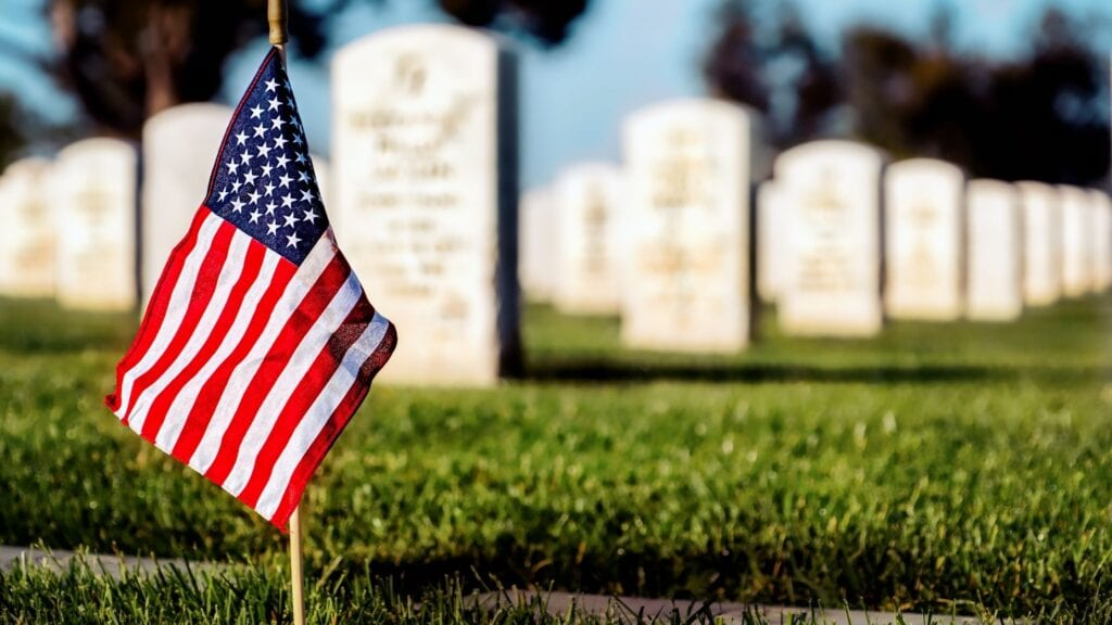 small american flag standing in the ground of a military cemetery on Memorial Day