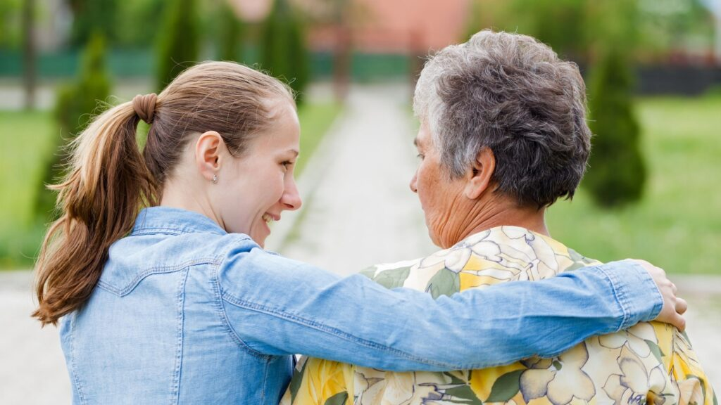 young woman assisting an elderly woman by walking with her arm around her shoulders