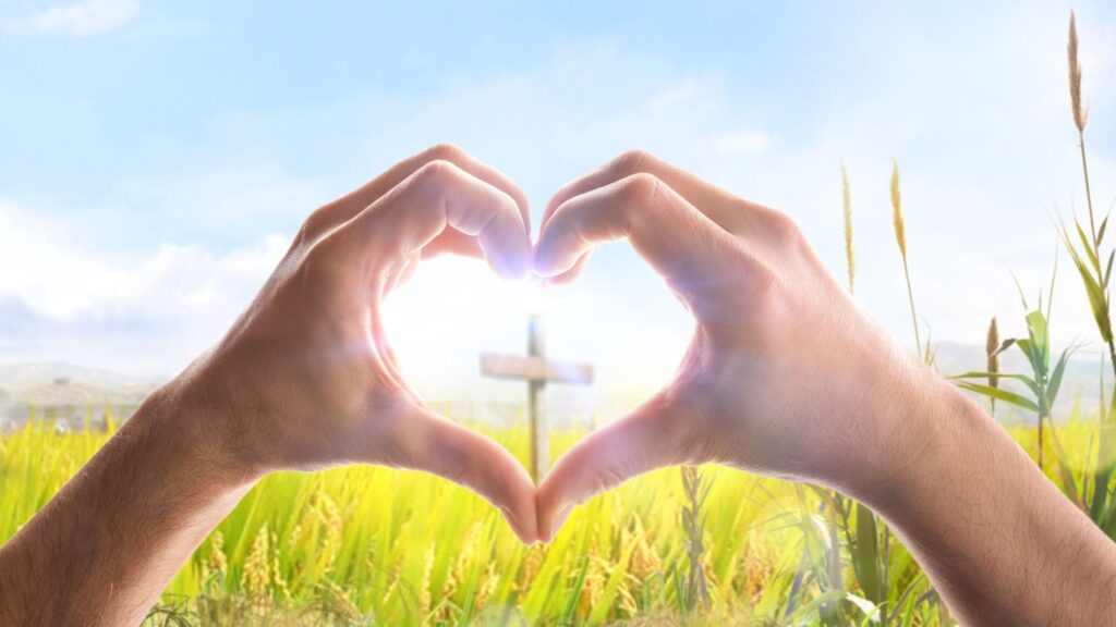 hands formed together into the shape of a heart with a cross in the center looking out over a field