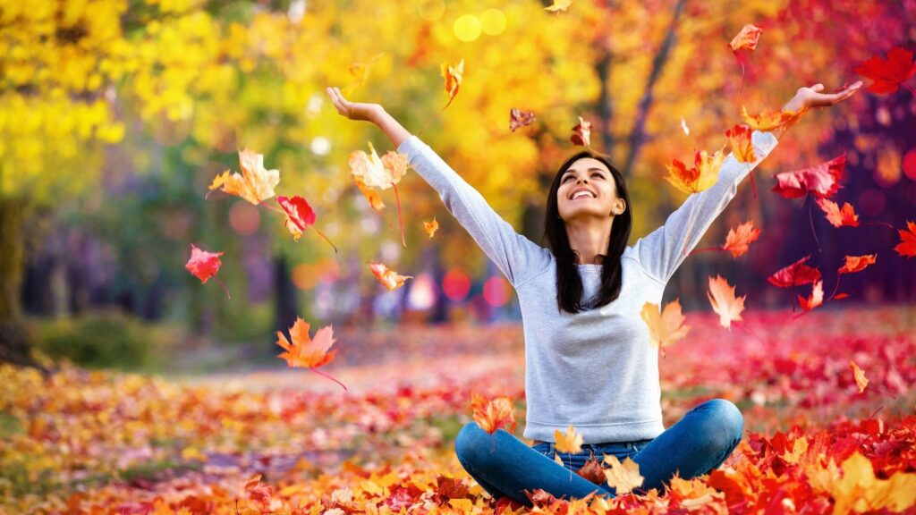 woman sitting outside in autumn throwing the fall leaves into the air
