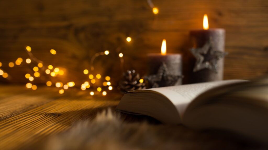 Advent candles on a table next to a book with lights twinkling in the background
