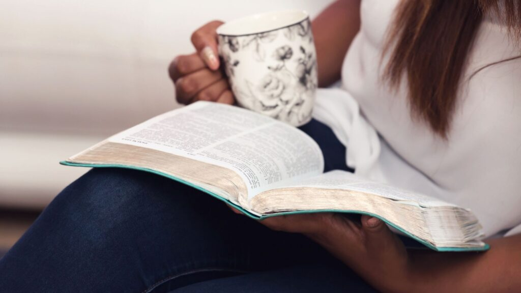 african american woman sitting with her bible open on her lap and drinking a cup of coffee