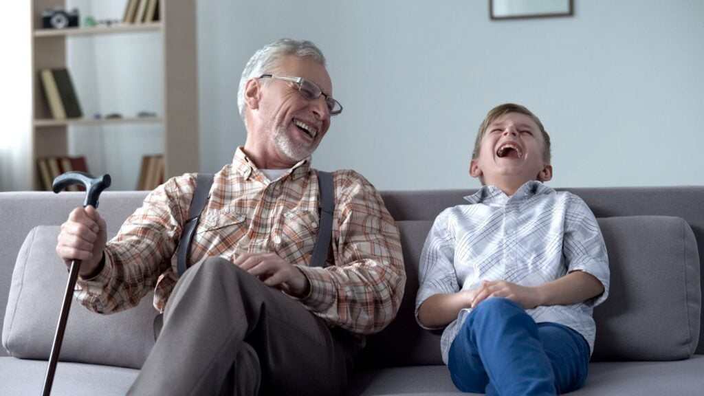 elderly man sitting on a couch laughing with his grandson