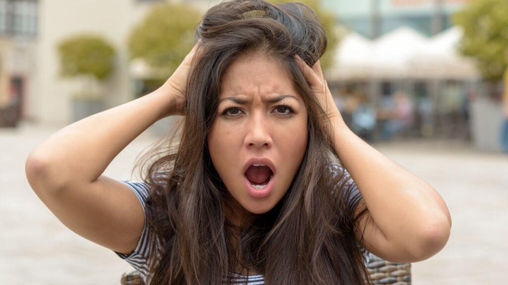 frantic woman grabbing her hair and head