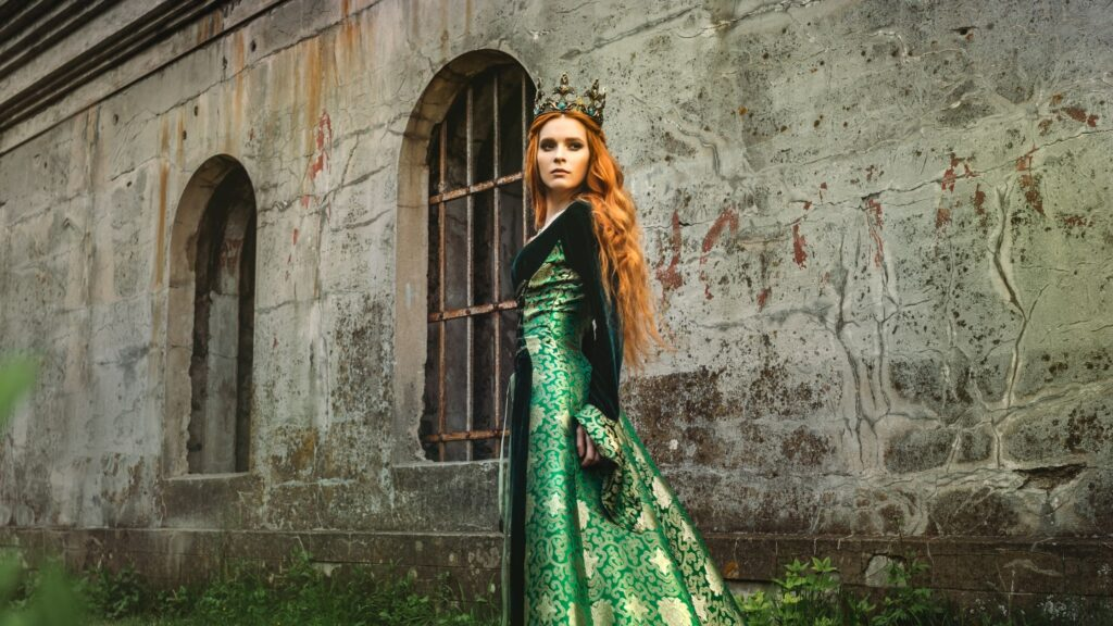 red haired queen wearing a green dress standing outside her castle