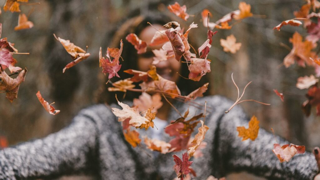 woman in a sweater tossing a pile of autumn leaves in the air