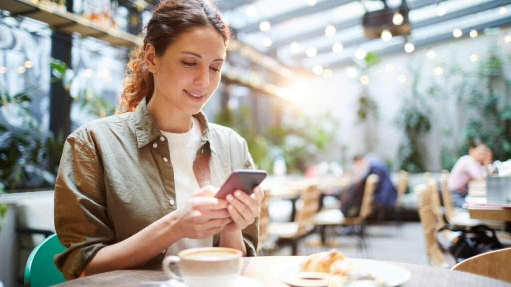 woman sitting at a coffee shop using her mobile phone