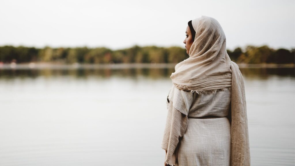 Biblical woman standing in a lake looking out over the water