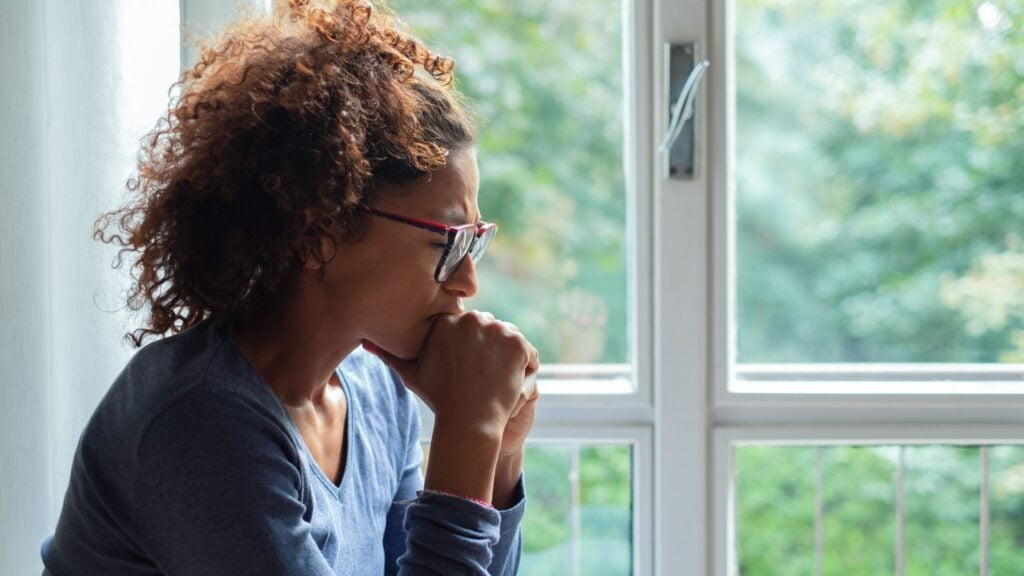 african american woman with hands together in prayer while looking out the window