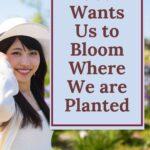 asian woman holding her bonnet while walking through a flower garden