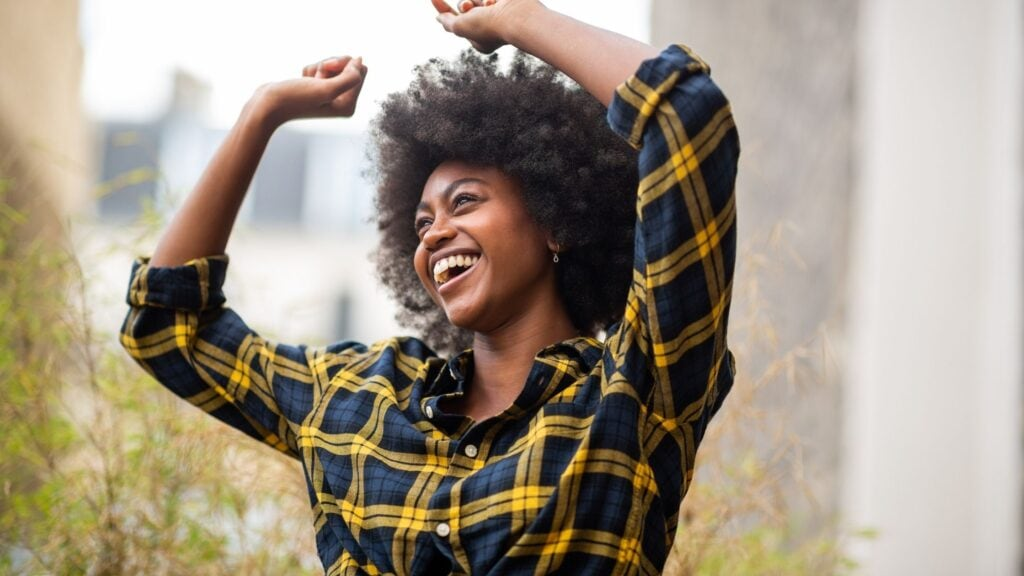 cheerful young carefree afro woman with arms raised and smiling outside