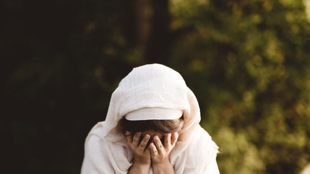 biblical woman in a robe with her hands over her face like she is crying