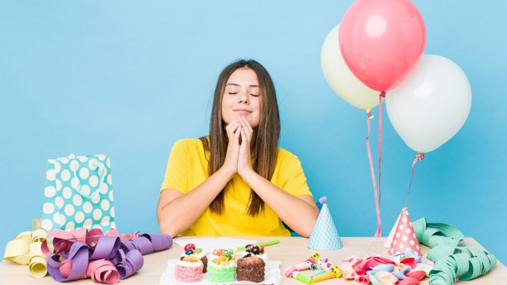 woman praying at her birthday party with gifts on the table