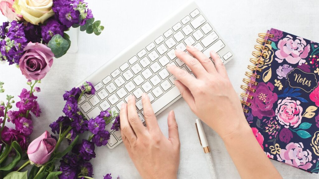 woman's hands typing on a keyboard next to flowers